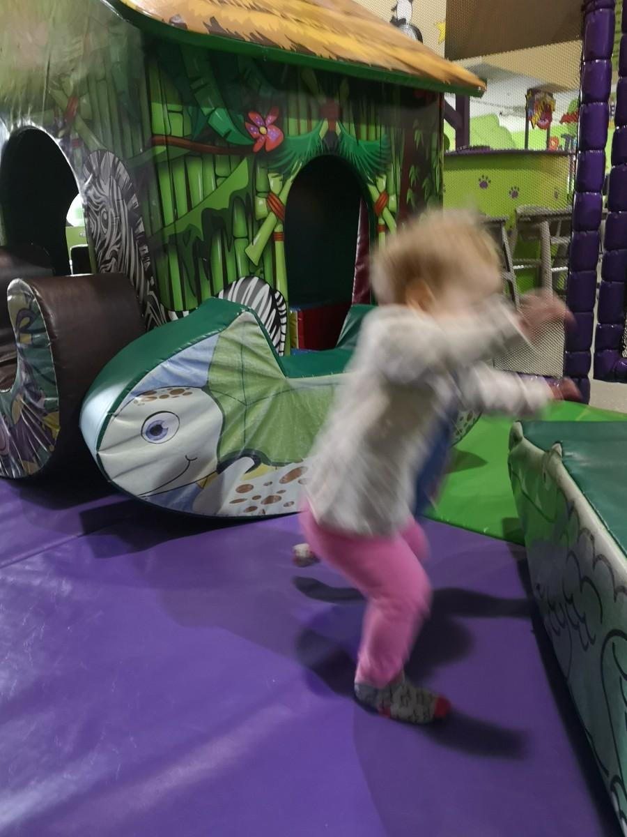 Toddler dashing between soft play foam shapes