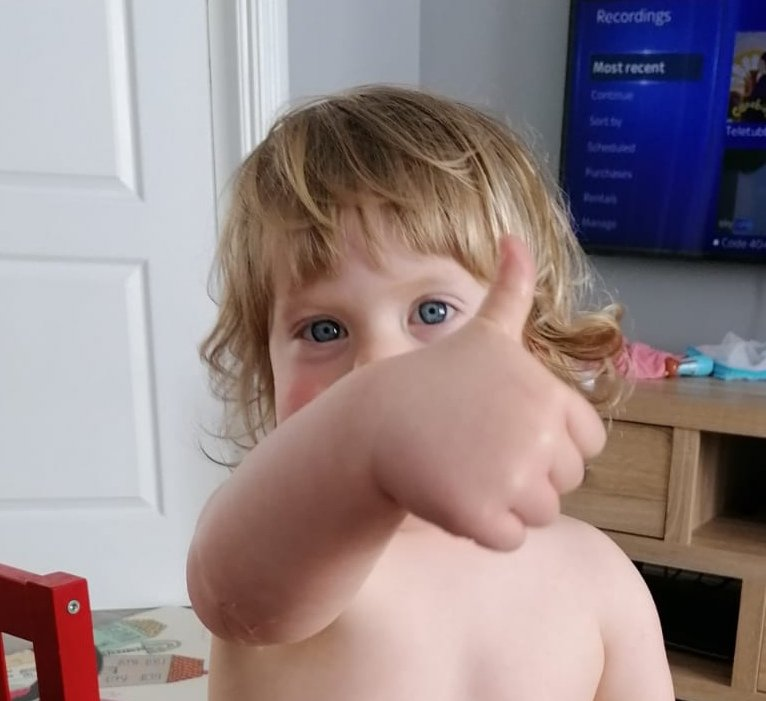 Toddler giving thumbs up to camera